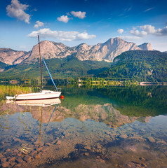 Bright sunny morning on the Grundlsee lake with white yacht