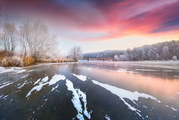 Picturesque winter sunset on the frozen lake.