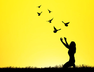 silhouette of bird flying into lady hand on beautiful background.freedom concept
