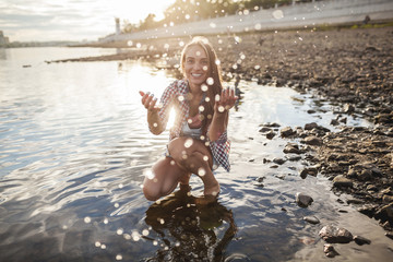 Happy young woman spalshing in a river at sunset