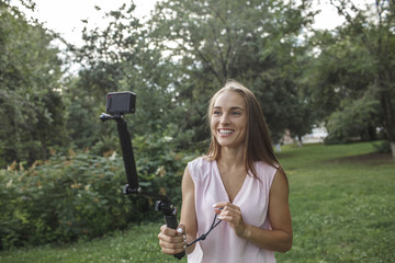 Smiling young woman taking a photo of herself on a meadow