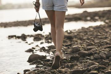 Woman holding a camera walking on stony beach