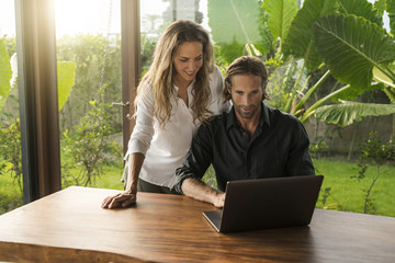 Smiling couple looking at laptop in design house surrounded by lush tropical garden