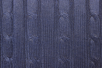 Knitted woolen texture. Dark blue sweater with a large weave.  Background.