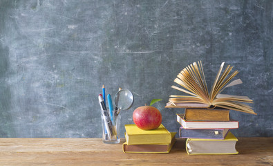 Back to school and education supplies, books, pens, on black board background