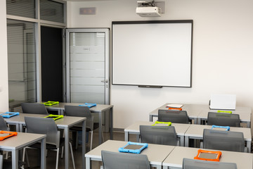 Modern classroom interior, with white board, work desks and chairs.