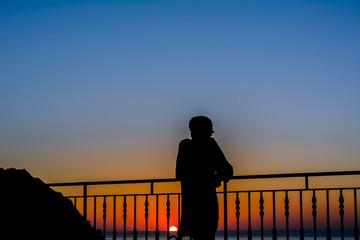 silhouette di una donna che guarda l'orizzonte al tramonto