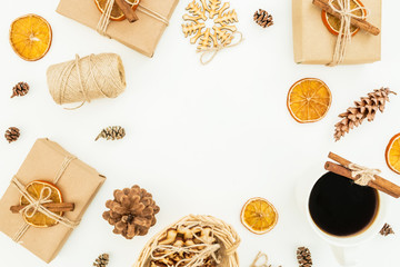 Round frame of Christmas or New Year decoration, craft gift box, coffee mug and pine cones on white background. Flat lay, top view