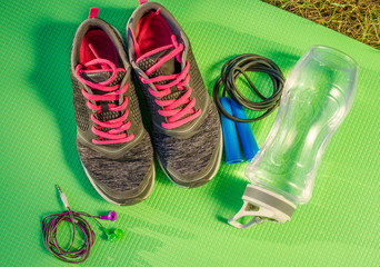 Sports and physical activity equipment and healthy food for diet on green background