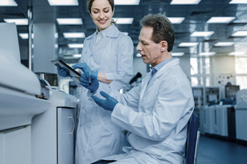 Scientific research. Smart handsome nice man sitting on the chair in the lab and holding a test tube while carrying out a scientific research