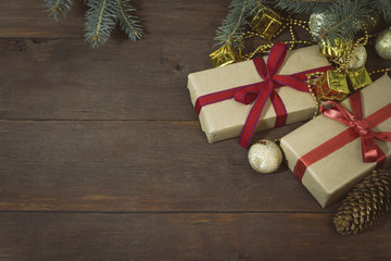 Packed gifts tied with red ribbons, two fir cones, spruce twigs, golden decorative toys on a wooden background