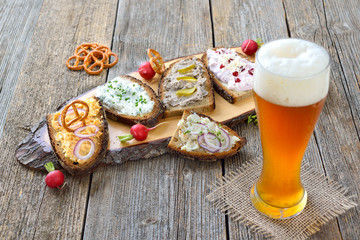 Brotaufstriche auf rustikalem Bauernbrot mit einem bayerischen Hefeweißbier rustikal serviert  -  Hearty Bavarian snack: various spreads on dark farmhouse bread served with a Bavarian yeast wheat beer