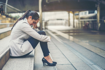Business woman stressed from work while sitting outdoors on the stairs, concept work life balance, burn out syndrome, press from colleagues.