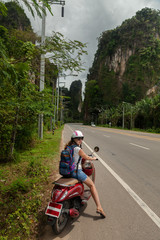 tourist woman sitting on classic scooter against the background of the mountains of Krabi Province, Thailand.