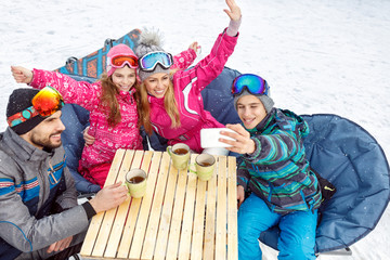 Boy taking family selfie in cafe on ski terrain