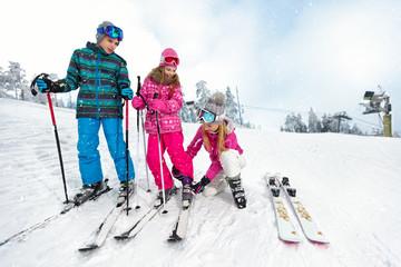 Mom with children on ski terrain preparing daughter for skiing