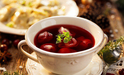 Christmas beetroot soup, borscht with small dumplings with mushroom stuffing in a ceramic bowl.  Traditional Christmas eve dish in Poland.