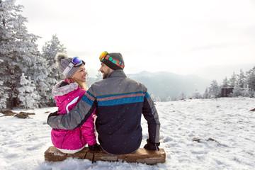 Couple in love sitting on ski terrain