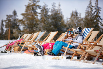 children at mountains in winter laughing and relax in sunbed chairs