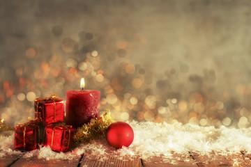 Weihnachtsdekoration aus roten Kugeln und Geschenkpäckchen vor einem warmen Hintergrund mit Textfreiraum
