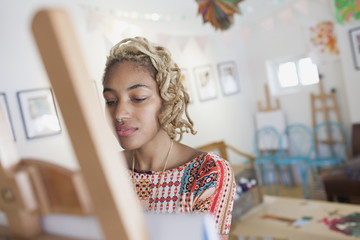 Young woman standing in front of an easel