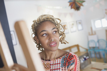 A young woman in front of an easel