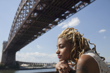 Side profile of a young woman beneath a bridge