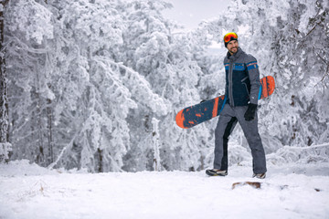 smiling man with ski mask holding his snowboard, extreme sport and winter holiday