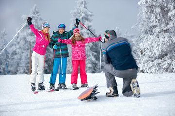 father taking picture of family on ski holiday in mountains