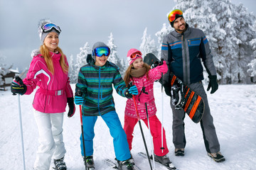 smiling family with ski and snowboard on ski holiday in mountains