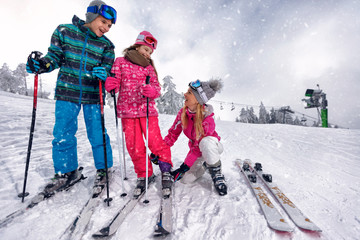 mother preparing for skiing her children on ski resort