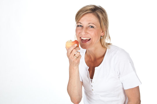 Blond cute woman eating an apple