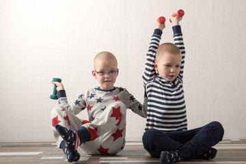 Two funny boys in sports clothes raise dumbbells up. Guys are actively engaged in fitness at home. Copy space.