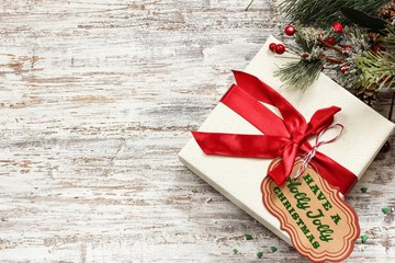 Xmas gift box with Tag on festive white wooden background / Christmas Holiday Concept ,Top down view