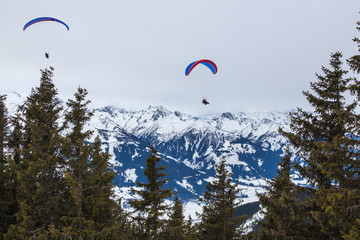 Paragliding above Alps covered with snow near Zell am See, Austria