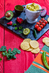 Mexican food concept:homemade guacamole, tortilla chips, salsa, chilli and fresh ingredients over vintage red rustic wooden background.