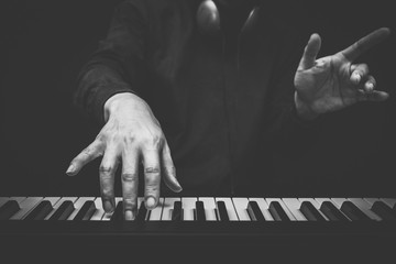 musician hands playing on piano keys, black and white