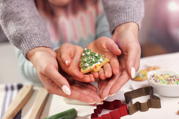 Midsection of mother and daughter hands holding Christmas cookies