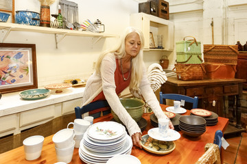 Caucasian woman arranging plates in store