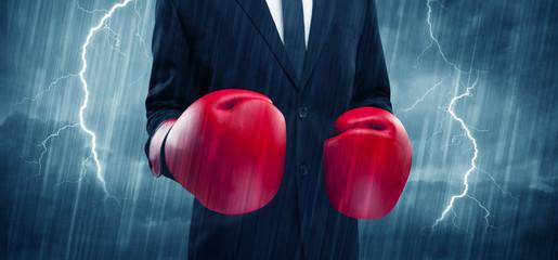 Businessman boxing in rain