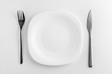empty white plate, fork and knife on a white background.