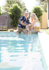 Caucasian couple smiling with legs in swimming pool
