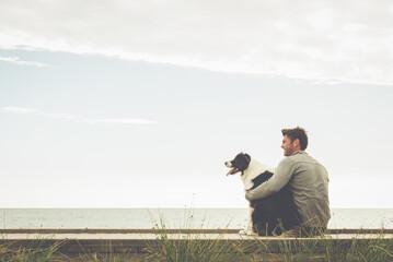 Caucasian man and dog sitting on boardwalk