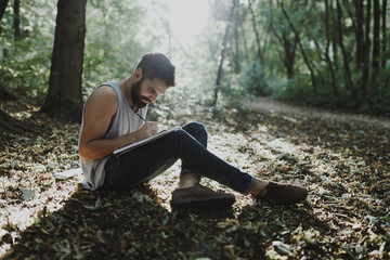 Caucasian man sitting in woods drawing on sketchpad