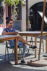 Man with prosthetic leg texting on cell phone at sidewalk cafe