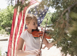 Caucasian girl playing violin near American flag