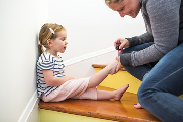 Caucasian mother painting toenails of daughter on staircase