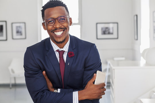 Black man with arms crossed in gallery