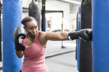 Black woman wearing boxing gloves hitting punching bag