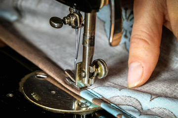Women hands of Seamstress Using Vintage Sewing Machine